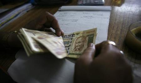 An employee counts currency notes at a cash counter inside a bank in Agartala August 9, 2011. REUTERS/Jayanta Dey/Files