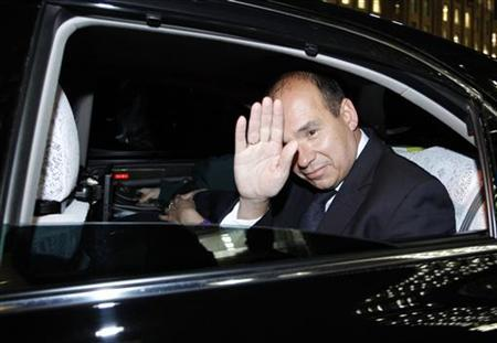 Former Olympus CEO Michael Woodford waves from a car window as he leaves at a news conference at the Japan National Press Club in Tokyo December 15, 2011. REUTERS/Issei Kato