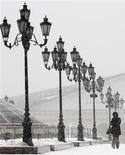 Женщина идет по заснеженной Манежной площади в Москве 29 декабря 2009 года. Агентство по страхованию вкладов прогнозирует замедление темпов прироста вкладов населения РФ в 2012 году из-за эффекта базы и возможных экономических рисков. REUTERS/Alexander Natruskin