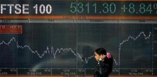 Прохожий идет мимо электронного табло с индексом  FTSE в Лондоне, 19 сентября 2008 г.  Европейские акции закрылись подъемом во вторник после хорошей статистики из Германии и США и удачного аукциона испанских облигаций, которые укрепили надежды инвесторов на улучшение экономического прогноза.  REUTERS/Andrew Winning