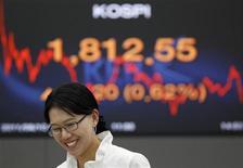 Валютный дилер Korea Exchange Bank на фоне табло с котировкой индекса KOSPI в дилерской комнате банка в Сеуле 10 августа 2011 года. Фондовые рынки Азии закрылись в среду ростом после хорошей макростатистики США и Германии, а также высокого спроса на облигации Испании, повысивших аппетит к риску, но рынок акций Китая упал из-за обвала котировок второго по размеру страховщика в мире. REUTERS/Jo Yong-Hak