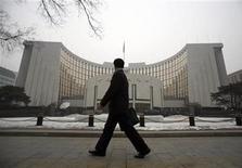 """Мужчина проходит мимо здания Народного банка Китая в Пекине 19 января 2010 года. Китай будет придерживаться осторожной денежно-кредитной политики в 2012 году и обеспечивать приемлемый рост """"общего социального финансирования"""", заявил глава центрального банка КНР Чжоу Сяочуань в среду. REUTERS/Loic Hofstedt"""