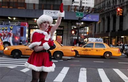 A woman dressed in a Santa costume hails a cab in New York, December 10, 2011.  REUTERS/Kena Betancur