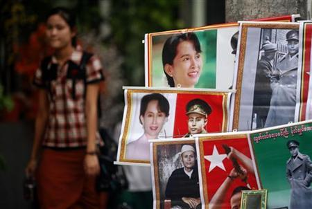 People walk past posters of Myanmar's pro-democracy leader Aung San Suu Kyi and her father and country's independence hero General Aung San offered for sale in central Yangon December 9, 2011. REUTERS/Soe Zeya Tun