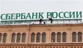 """Рабочие чистят крышу, на которой установлена реклама Сбербанка, в Санкт-Петербурге 11 марта 2011 года. Крупнейший госбанк РФ Сбербанк приобрел швейцарскую банковскую """"дочку"""" нефтяной компании Лукойл - банк SLB Commercial Bank, сообщил Сбербанк. REUTERS/Alexander Demianchuk"""