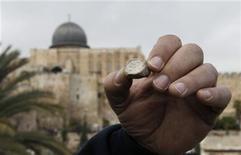 <p>Arqueólogos israelíes anunciaron el hallazgo de un sello de arcilla de 2.000 años de antigüedad cerca del Muro de los Lamentos en Jerusalén, lo que confirma los relatos escritos de prácticas rituales en el templo bíblico judío. En la foto del domingo, un arqueólogo muestra un sello. Dic 25, 2011. REUTERS/Baz Ratner</p>