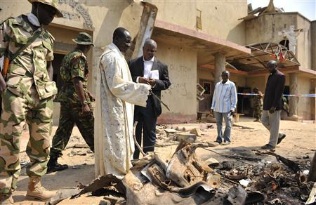 A member of the clergy guides security forces through the scene of a car bomb explosion at  St. Theresa Catholic Church at Madalla, Suleja, just outside Nigeria's capital Abuja, December 25, 2011. Islamist militant group Boko Haram said it planted bombs that exploded on Christmas Day at churches in Nigeria, one of which killed at least 27 people on the outskirts of the capital. REUTERS/Afolabi Sotunde