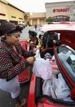 Дженнифер Гриффин из Окленда, штат Калифорния, згружает в машину покупки, сделанные в Bay Fair Mall в Сан-Леандро 26 декабря 2011 года. Американские рителейры надеются на высокий объем продаж в первый день после Рождества - третий по активности покупателей день праздничного сезона. REUTERS/Dino Vournas