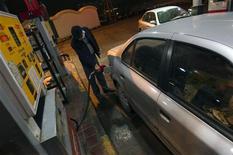 Мужчина заправляет автомобиль в Тегеране 19 декабря 2010 года. Иран подписал соглашение с Афганистаном о поставках ему одного миллиона тонн бензина, дизельного и авиационного топлива, начиная со следующего года, сообщило официальное информационное агентство Ирана IRNA. REUTERS/Morteza Nikoubazl