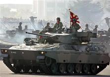 Танки Сил самообороны Японии во время парада в учебном центре в Асаке 7 ноября 2004 года. Япония сняла запрет на экспорт военного оборудования во вторник, открыв компаниям новые рынки в попытке помочь нации выжать как можно больше из оборонного бюджета, сообщило информационное агентство Kyodo. REUTERS/Yuriko Nakao