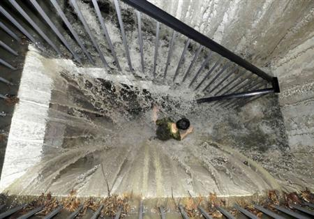 A resident runs on a flooded stairway as floodwater pours into an underground garage amid heavy rainfalls in Chengdu, Sichuan province in this July 3, 2011 file photo. REUTERS/China Daily/Files