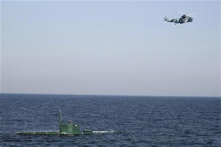 12月27日、イランは同国の原油輸出に対し制裁措置が加えられた場合には、ホルムズ海峡を封鎖し原油輸送を停止させると警告した。写真は同日、ホルムズ海峡を航行する潜水艦の上空を旋回するヘリコプター(2011年 ロイター/IIPA/Ali Mohammadi)