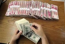 Работник отделения банка Bank of China в Хэфэе пересчитывает долларовые банкноты 16 октября 2009 года. Министерство финансов США вновь остереглось называть Китай валютным манипулятором, но отчитало страну за то, что она недостаточно быстро проводит валютные реформы. REUTERS/Stringer