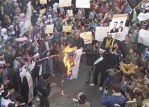 """Демонстранты сжигают изображение сирийского президента Башара Асада в Хомсе 16 декабря 2011 года. Некоторые районы города Хомс находятся в плохом состоянии, однако ничего """"ужасающего"""" там замечено не было, заявил глава миссии Лиги арабских государств, проверяющей выполнение Дамаском условий заключенного с ЛАГ соглашения. REUTERS/Handout"""