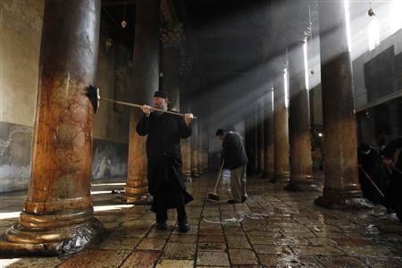 A member from the Greek Orthodox clergy (L) and a Palestinian use diesel to scrub the floor and columns of the Church of the Nativity, the site revered as the birthplace of Jesus, in the West Bank town of Bethlehem December 28, 2011. Credit: Reuters/Ammar Awad