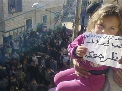 A girl holds a sign reading: 'People want a no fly zone' during a demonstration against Syrian President Bashar al-Assad in Homs, December 27, 2011.   REUTERS-Handout