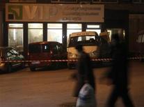 Пешеходы проходят мимо подвергшегося ограблению отделения Приватбанка в Донецке 29 декабря 2011 года. Пять человек погибли в четверг во время вооруженного ограбления офиса по обслуживанию состоятельных клиентов крупнейшего банка Украины - Приватбанка в Донецке. REUTERS/Valeriy Bilokryl