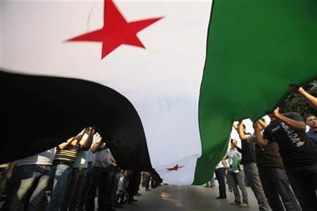 Syrians living in Egypt wave a large Syrian national flag and shout slogans against Syrian President Bashar al-Assad during a protest before the Arab League foreign ministers emergency meeting, at the Arab League headquarters in Cairo November 2, 2011. REUTERS/Mohamed Abd El-Ghany/Files