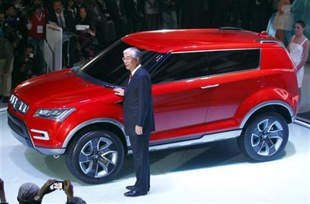 Shinzo Nakanishi, chief executive and managing director of Maruti Suzuki poses with company's new compact SUV XA Alpha car after unveiling it at Delhi Auto Expo in New Delhi January 5, 2012. REUTERS/Adnan Abidi