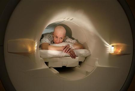 A cancer patient lies inside the tube of a magnetic resonance imaging scanner during an MRI examination of her breasts at Georgetown University Hospital in Washington May 23, 2007. REUTERS/Jim Bourg
