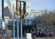 Казахский спецназ проходит под плакатом с изображением президента Нурсултана Назарбаева, который был частично сожжен во время беспорядков в Жанаозене. Фотография сделана 19 декабря 2011 года. Казахстан отменил проведение парламентских выборов, назначенных на 15 января, в городе нефтяников Жанаозен на западе страны, сообщила Центральная избирательная комиссия в пятницу. REUTERS/Vladimir Tretyakov