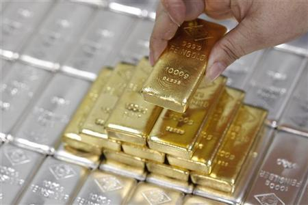 An employee picks up a gold bar at the Austrian Gold and Silver Separating Plant 'Oegussa' in Vienna August 26, 2011. REUTERS/Lisi Niesner