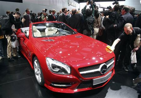 A worker removes fingerprints from the 2013 Mercedes Benz SL on the first press preview day at the North American International Auto Show in Detroit, Michiganon the first press preview day in Detroit, Michigan, January 9, 2012.  REUTERS/Rebecca Cook