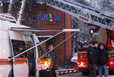 Сотрудники аварийно-спасательных служб стоят возле московского ресторана, в котором прогремел взрыв 9 января 2012 года. Десятки человек пострадали и двое погибли после взрыва в итальянском ресторане на юго-западе Москвы, который разнес крышу здания, металлические конструкции и выбил окна. REUTERS/Tatyana Makeyeva