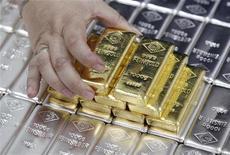 Сотрудник завода Oegussa в Вене поднимает слиток золота 26 августа 2011 года. Цены на золото растут, так как ослабление доллара по отношению к евро делает драгметалл привлекательным вложением для инвесторов за пределами США. REUTERS/Lisi Niesner