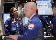 Трейдеры на торгах Нью-Йоркской фондовой биржи 6 января 2012 года. Фондовый рынок США открылся ростом во вторник благодаря повышению цен на акции сырьевого сектора после объявления ожиданий компании Alcoa и благодаря данным о росте продаж в розничных сетях США на прошлой неделе. REUTERS/Brendan McDermid