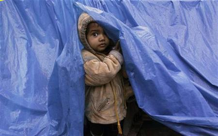 A child looks out from his shelter made up of tarpaulin at a pavement on a cold winter morning in Noida January 6, 2012. REUTERS/Parivartan Sharma
