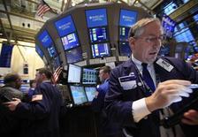 Трейдеры на торгах Нью-Йоркской фондовой биржи 10 января 2012 года. Уолл-стрит достигла пятимесячного максимума во вторник благодаря сырьевым акциям, укрепившимся после хорошего прогноза, сделанного Alcoa, и банковским бумагам. REUTERS/Brendan McDermid