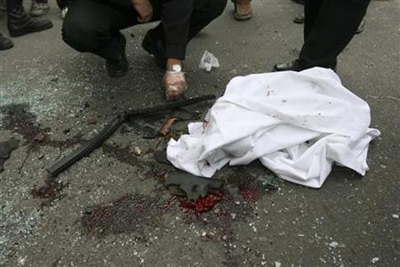 EDITORS' NOTE: Reuters and other foreign media are subject to Iranian restrictions on leaving the office to report, film or take pictures in Tehran. A policeman checks the remains of a bombed car belonging to Iranian nuclear scientist Mostafa Ahmadi-Roshan on a blood-stained ground at the blast site outside a university in northern Tehran January 11, 2012. REUTERS/Fars News/Meghdad Madadi