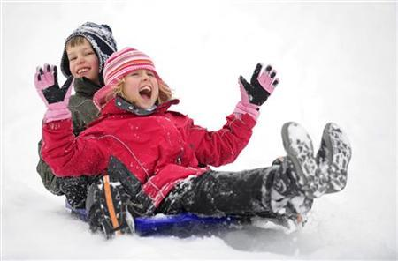 Children enjoy sledging in the snow in Pitlochry, Scotland January 9, 2010. REUTERS/Russell Cheyne
