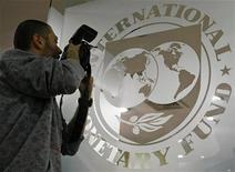 A photographer takes pictures through a glass carrying the International Monetary Fund (IMF) logo during a news conference in Bucharest, Romania. March 25, 2009.     REUTERS/Bogdan Cristel
