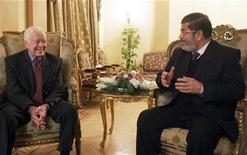 Former U.S. President Jimmy Carter (L) speaks with Mohamed Mursi, the head of the Muslim Brotherhood's Freedom and Justice Party, during their meeting in Cairo, Egypt. January 12, 2012. REUTERS/Stringer