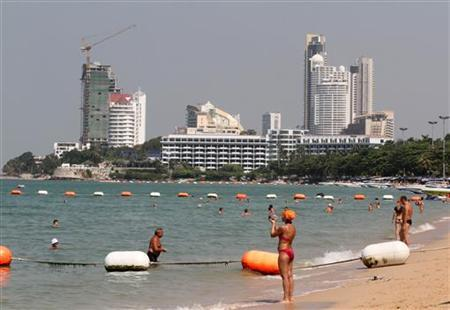 Tourists relax at the beach of Pattaya, nearly 150 km (90 miles) east of Bangkok January 26, 2011. REUTERS/Chaiwat Subprasom