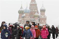 Люди на заснеженной Красной площади на фоне Покровского собора в Москве 29 декабря 2010 года. Пятничное потепление в Москве сойдет на нет в наступающие выходные - в субботу и воскресенье столичных жителей ждут легкие морозы и снег. REUTERS/Denis Sinyakov