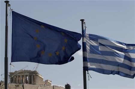 A European Union (L) and Greek flag wave in front of the Parthenon temple in Athens April 11, 2011. REUTERS/John Kolesidis