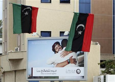 A billboard carrying the slogans 'Today we reconcile together' and 'Today Tripoli has a new heart beat' is seen behind Kingdom of Libya flags in Tripoli, December 14, 2011. REUTERS/Ismail Zitouny/Files