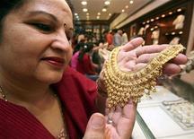 Женщина держит золотое ожерелье в ювелирном магазине в Чандигархе 26 октября 2008 года. Спрос на золотые ювелирные изделия в Индии - одном из крупнейших в мире рынков золота - повысился на 5-7 процентов в 2011 году и вырастет на 10-15 процентов в этом году благодаря снижению цен на золото, сказал глава одной из крупнейших в Индии розничных компаний по продаже ювелирных изделий. REUTERS/Ajay Verma