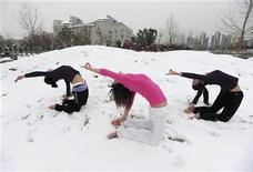 <p>Local residents practise yoga after a snowfall at a park in Wuhan, Hubei province January 6, 2010. REUTERS/Stringer</p>