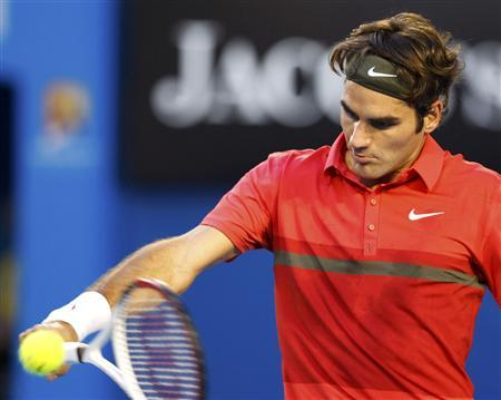Roger Federer of Switzerland hits a return to Alexandre Kudryavtsev of Russia during their men's singles match at the Australian Open tennis tournament in Melbourne January 16, 2012.  REUTERS/Tim Wimborne