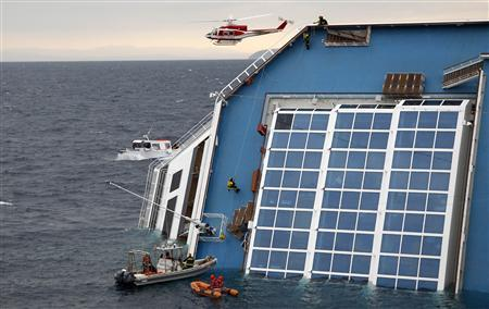 Rescue workers climbs up the capsized Costa Concordia cruise ship that ran aground off the west coast of Italy at Giglio island January 16, 2012.  REUTERS/ Max Rossi
