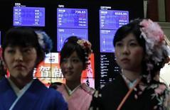 Женщины в кимоно на фоне экранов с фондовыми котировками на Токийской фондовой бирже 4 января 2012 года. Фондовые рынки Азии выросли по итогам торгов во вторник благодаря превысившей прогноз статистике ВВП Китая, которая смягчила опасения по поводу последствий европейского кризиса для мировой экономики. REUTERS/Kim Kyung-Hoon