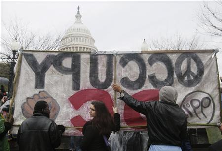 Occupy Congress/DC protesters hold up a banner in front of the U.S. Capitol during a rally in Washington, January 17, 2012.   REUTERS/Gary Cameron
