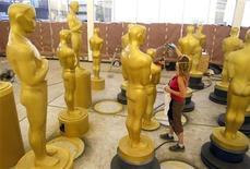 """Женщина красит увеличенные копии статуэтки премии """"Оскар"""" в Голливуде 15 октября 2010 года. Работа иранского режиссера Асгара Фархади """"Развод Надера и Симин"""" попала в число девяти картин, претендующих на премию """"Оскар"""" лучшему иностранному фильму. REUTERS/Lucy Nicholson"""