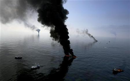Smoke billows from a controlled burn of spilled oil off the Louisiana coast in the Gulf of Mexico coast line, June 13, 2010.  REUTERS/Sean Gardner