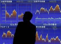 Мужчина смотрит на экран с динамикой индексов на фондовой бирже Nikkei около брокерской конторы в Токио 9 июня 2010 года. Глобальные инвесторы относятся сейчас с большим доверием к развивающимся рынкам, а в России отдают предпочтение точечным вложениям в противовес покупки корзины бумаг, следует из статистики EPFR Global, на которую ссылаются Уралсиб и Альфа-банк. REUTERS/Yuriko Nakao