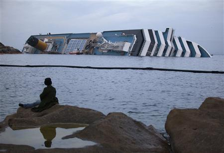 A woman watches the Costa Concordia cruise ship that ran aground off the west coast of Italy at Giglio island at dusk January 19, 2012.  REUTERS/ Paul Hanna